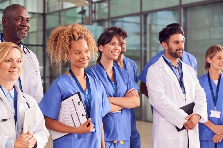 Smiling Medical Team Standing In Modern Hospital Building